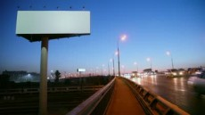 stock-footage-empty-advertising-billboard-on-sidelines-of-road-with-traffic-near-railroad-at-evening-fast-motion